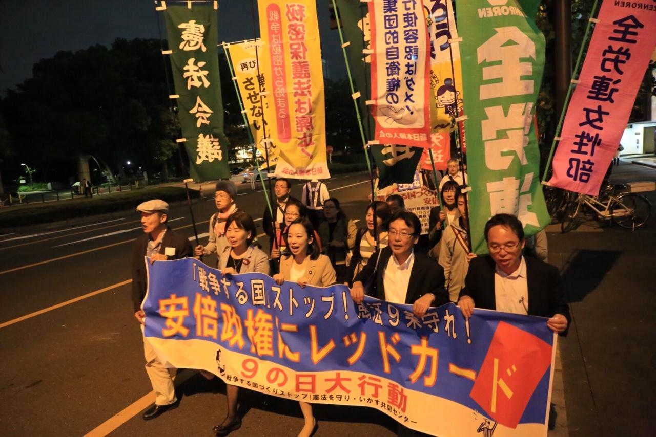 「安倍政権にレッドカード」の横断幕を掲げ、デモ行進する人たち=9日、東京都内