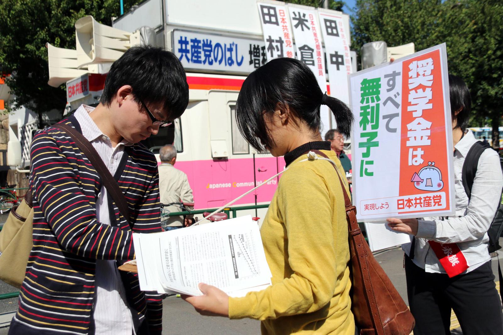 署名の呼びかけに応じる学生(左)=17日、東京都新宿区の早稲田大学前