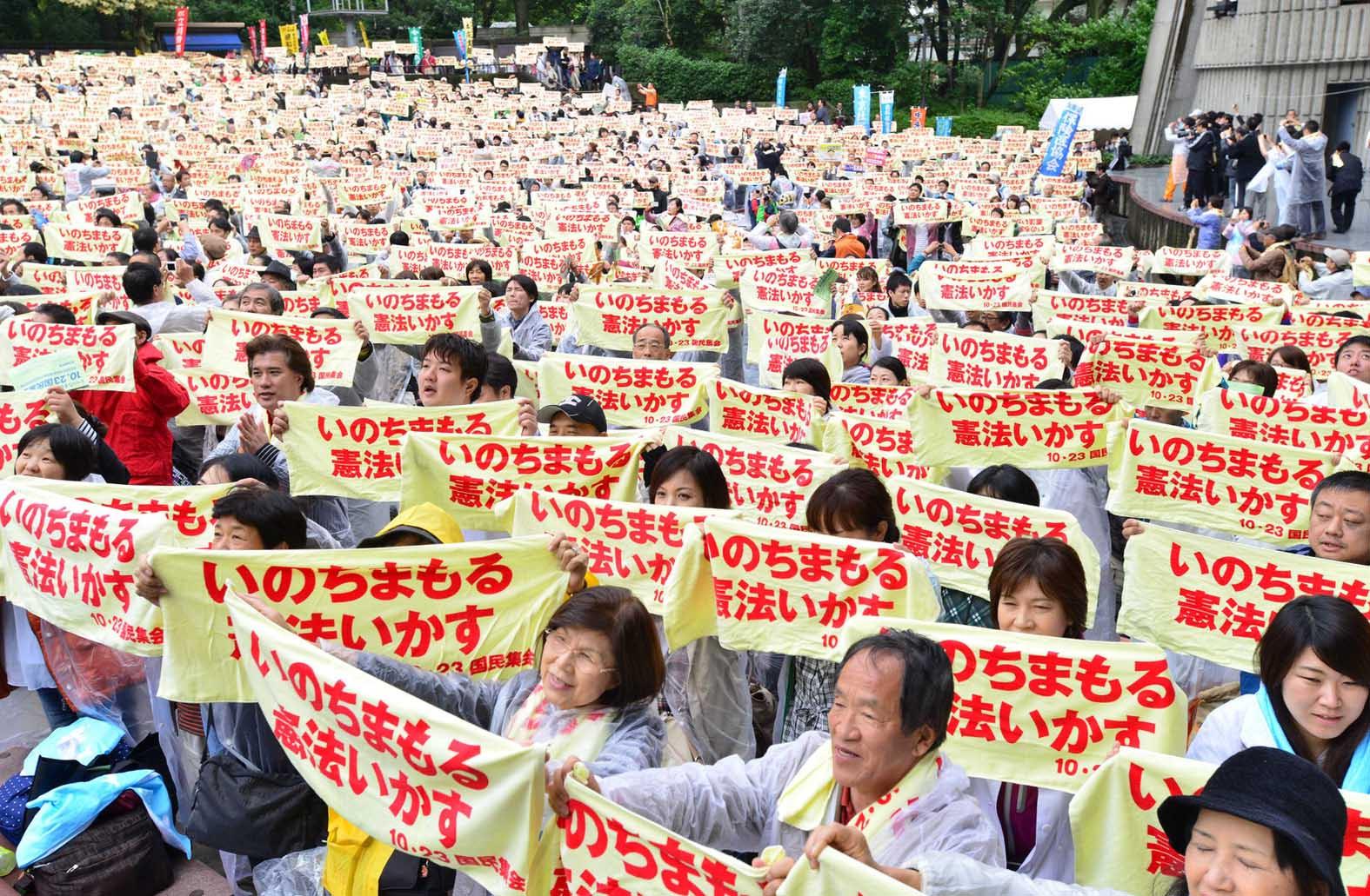 「いのちまもる・憲法いかす」とアピールする参加者=23日、東京・日比谷野外音楽堂