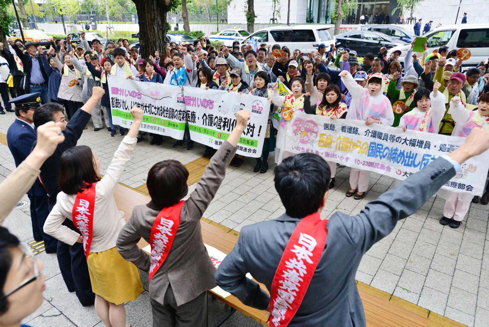 「がんばろう」とこぶしをあげる国民集会の参加者と日本共産党国会議員団=23日、参院議員面会所前