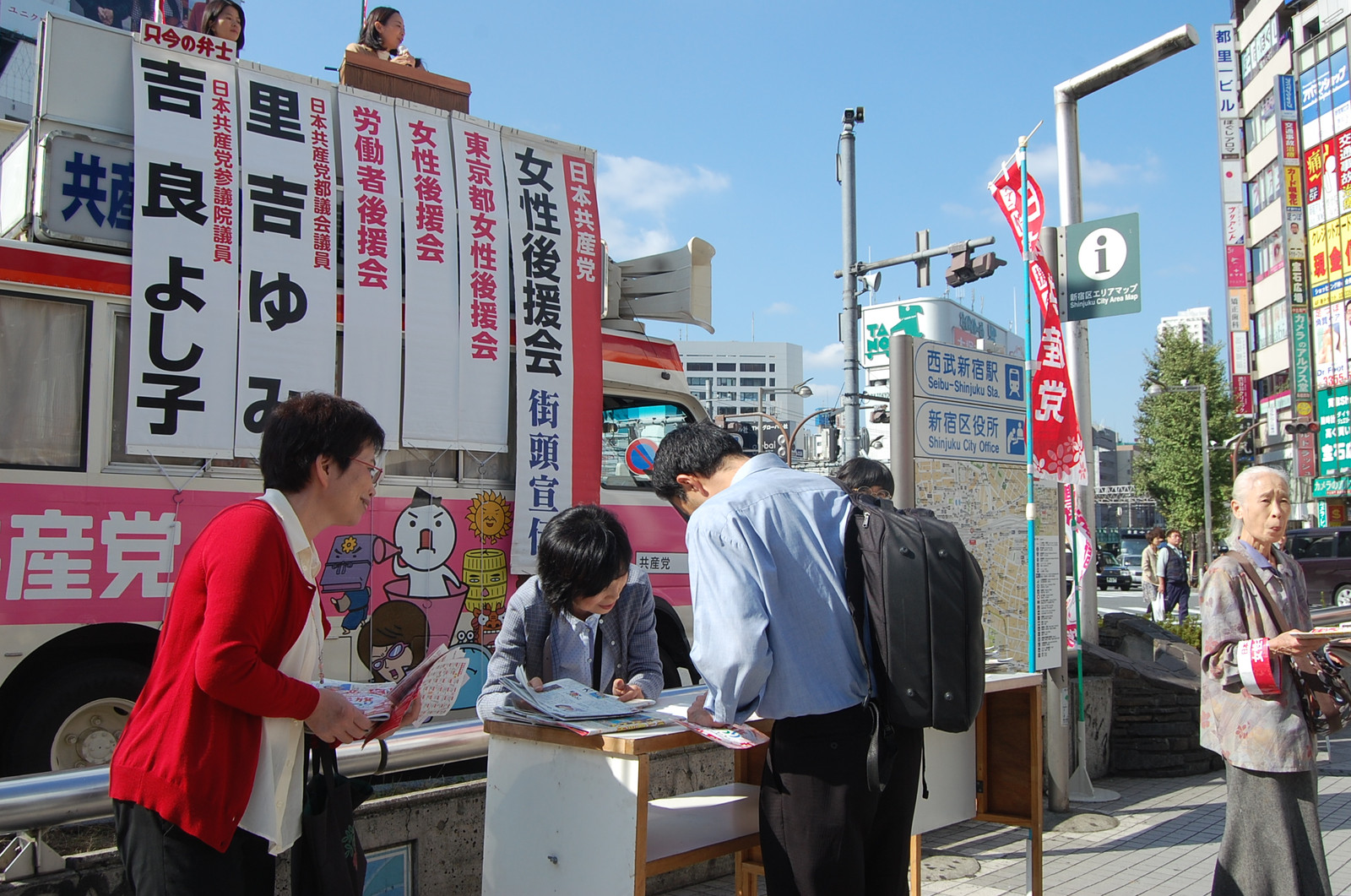 日本共産党の全国・全都女性後援会の呼びかけにこたえ、署名する男性=24日、東京・新宿駅前