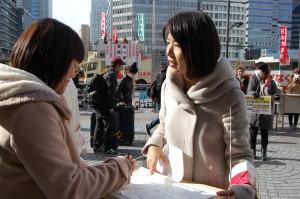 日本共産党女性後援会が呼びかけた署名にこたえる女性=16日、東京・新宿駅前