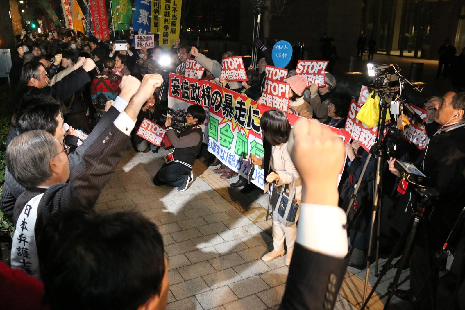 安倍政権の暴走をやめさせようとこぶしを上げ唱和する人たち=26日、国会前