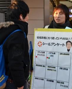 「安倍政権にもう黙っていられない!」のシールアンケートで対話する民青同盟員(右)=12日