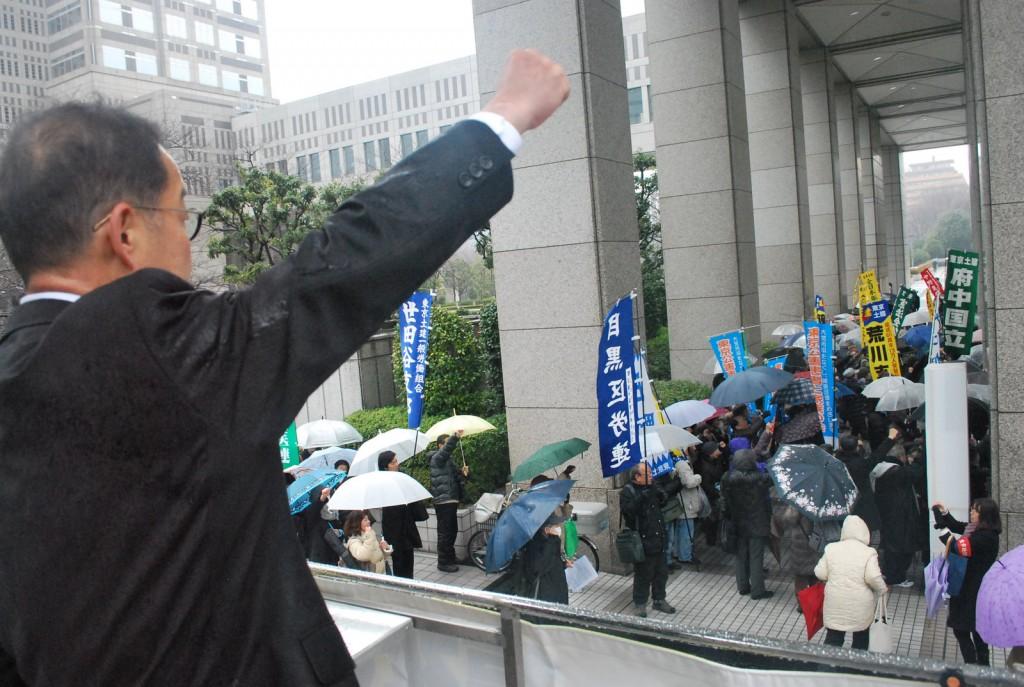 都庁に向かってアピールする松村友昭都議(左)と参加者ら=18日、東京都庁