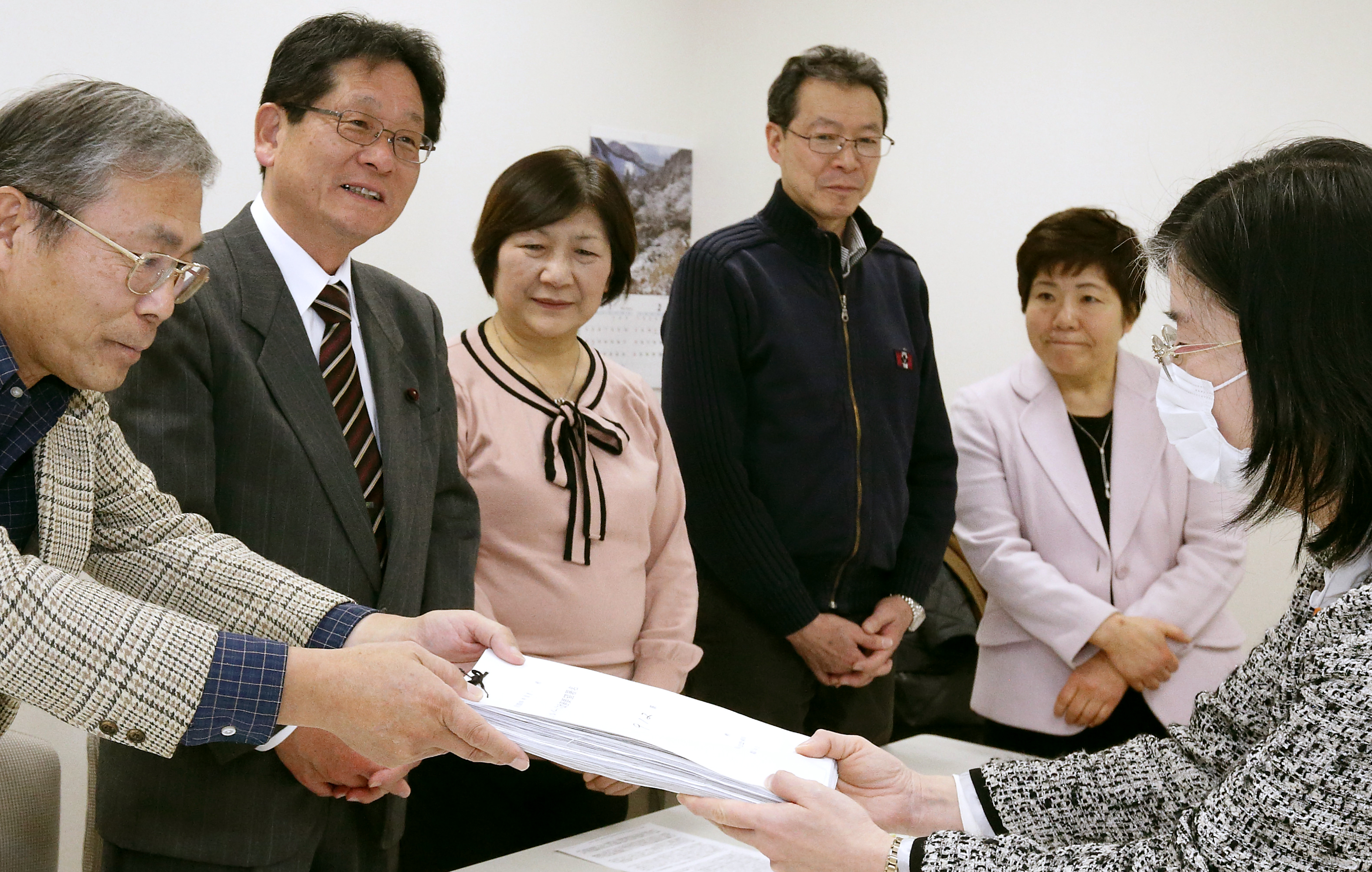署名を提出する後援会員。すがや俊一区議(左から2人目)、あぜ上三和子都議(同5人目)も同席=26日、都庁