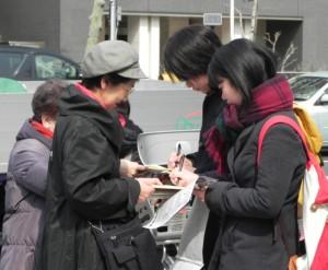 築地市場の豊洲移転に反対する署名に応じる人たち(右)=14日、東京都中央区
