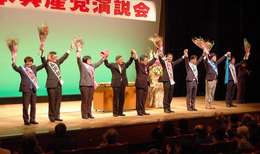 花束の激励を受ける区議候補と小池氏、植木氏=19日、東京都中野区
