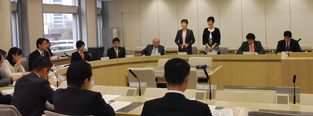 国保条例に賛成して起立する大山とも子、和泉なおみ両都議=20日、東京都議会