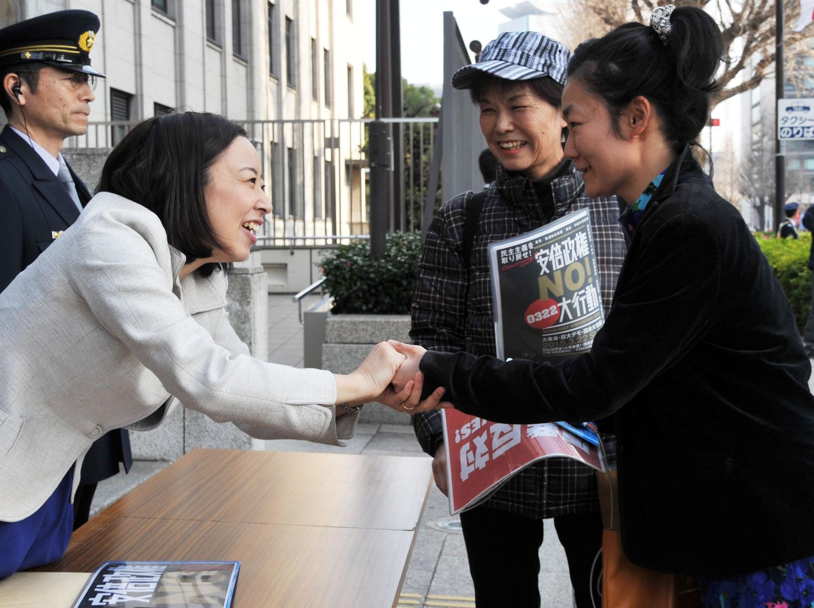吉良よし子参院議員(左)と激励の握手をする大行動参加者=22日、参院議員面会所前