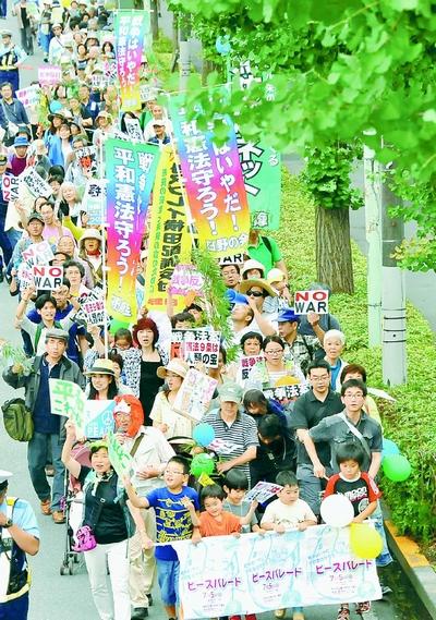 「戦争法案反対」「憲法守れ」と声をあげて歩くピースパレード参加者=5日、東京都日野市