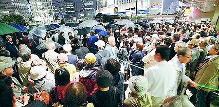 (写真)志位和夫委員長の街頭演説を聞く人たち=25日、東京・新宿駅西口