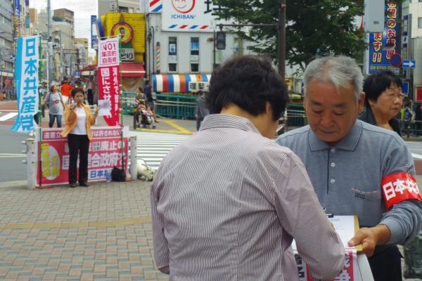 「提案」リーフを配布し、戦争法廃止の署名を集めた品川地区委員会の宣伝。マイクを握るのは鈴木ひろ子区議=29日、大井町駅前(「しんぶん赤旗」提供)
