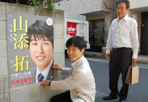 萬立区議(右)らとポスター張りに取り組む山添氏=3日、東京都文京区