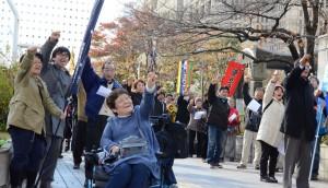 都庁に向かって声を上げる開会日行動の参加者ら=1日、東京都庁(「しんぶん赤旗」提供)