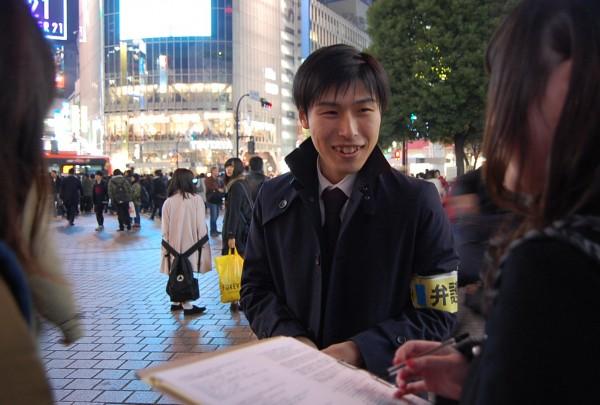 アンケートに応える女性と対話する山添氏(中央)=9日夜、渋谷駅まえ(「しんぶん赤旗」提供)
