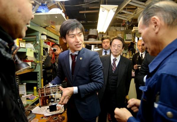 開発中の発電機を手にする山添候補(中央)=21日、東京都大田区(「しんぶん赤旗」提供)