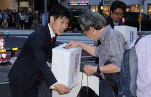 山添氏(中央)らの呼び掛けに応じて募金する人=18日、JR新宿駅南口(「しんぶん赤旗」提供)