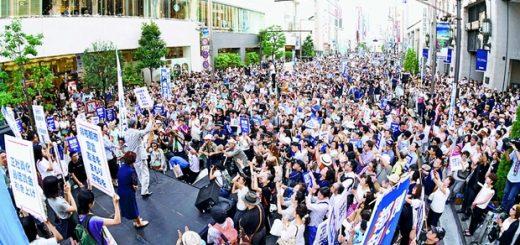 プラカードを掲げた鳥越俊太郎都知事候補の訴えを聞く人たち=24日、東京都新宿区