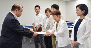 労働局の担当者(左)に申し入れ書を渡す、かち都議(右から2番目)と党都議団=3日、東京都千代田区
