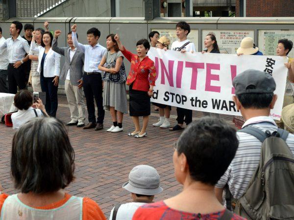野党3党や学者、市民がトークリレーで訴える街頭宣伝で、参加者とそろって「安 保法廃止」とコールするゲストスピーカーの各氏=21日、東京都多摩市