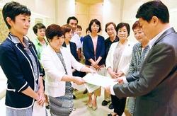 (写真)野田数(かずさ)都知事特別秘書(右)に提言を手渡す党都議団=8日、東京都庁
