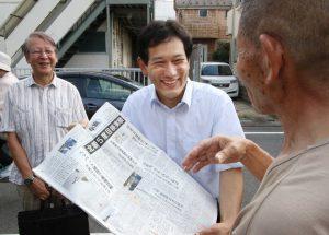 「赤旗」日刊紙の見本紙を示して購読を訴える宮本徹衆院議員(中央)ら=10日、東京都久留米市
