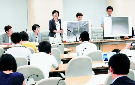 豊洲新市場の地下の写真パネルを示して記者会見する日本共産党都議団=12日、都庁