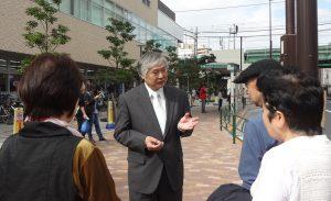 街頭で区民と対話する、もぎ正道区長候補(中央)=東京都荒川区(「しんぶん赤旗」提供)