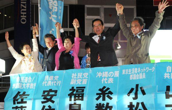手を上げて声援にこたえる(右から)佐藤、志位、福島、安住、小松の各氏=20日、東京・池袋駅西口(「しんぶん赤旗」提供)