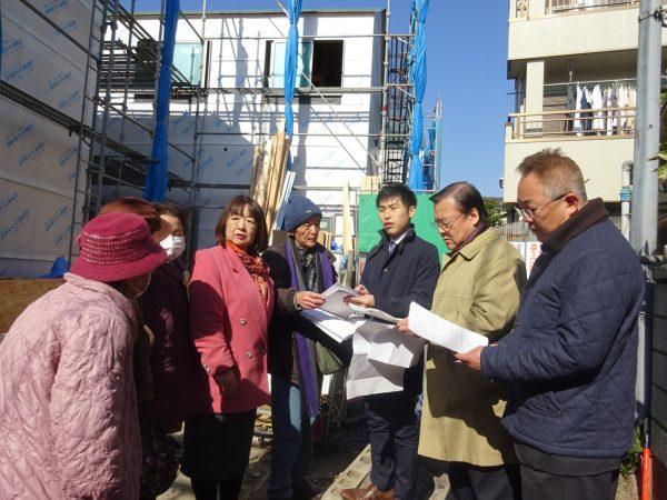 「重層長屋」の建設現場を視察し、住民らから話を聞く山添氏(右から3人目)=1日、東京都足立区