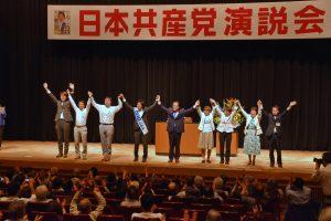 会場の声援にこたえる市田氏(右から5人目)=白石都議候補(その左)と品川区議ら=16日、東京都品川区