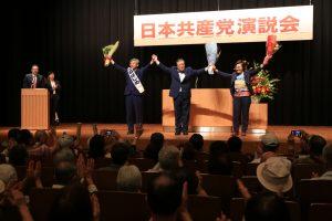 満場の聴衆の声援に応える(左から)そねはじめ都議、市田忠義副委員長、池内さおり衆院議員=20日、東京都北区