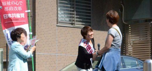 演説する福手候補に握手を求める区民と、関川区議=30日、東京都文京区