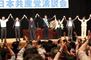 聴衆の声援に応える小池晃書記局長(左から3人目)、中野あきと都議候補(同4人目)ら=10日、東京都日野市