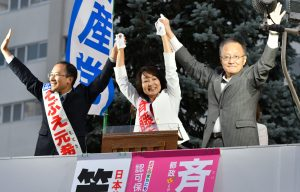 笠井亮政策委員長(右)と共に聴衆の声援に応える斉藤まりこ都議候補(中)。左はそぶえ元衆院候補=14日、東京都足立区