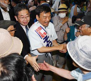 激励にこたえる小池晃書記局長(左)とそねはじめ都議候補=23日、東京都北区