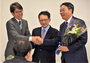 日本共産党港地区委員会の報告会で握手をかわす(右から)海江田、冨田、石沢の各氏