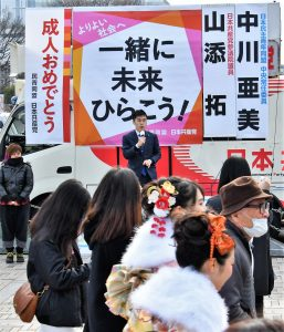新成人を激励し、訴える山添参院議員と民青の中川さん(左)=8日、東京都渋谷区