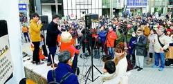 生活保護を引き下げるなと、「エキタス」と「もやい」の街頭宣伝を聞く人たち=28日、東京・新宿駅東口
