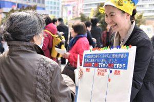 シールボードを使い対話する宣伝参加者(右)=2日、東京・新宿駅西口