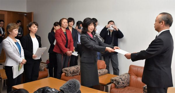 高橋市長(右)にセクハラ疑惑の解明を求める声明文書を手渡す女性議員有志=12日、東京都狛江市庁