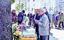 追悼碑に献花し手を合わせる集会参加者=10日、東京都台東区