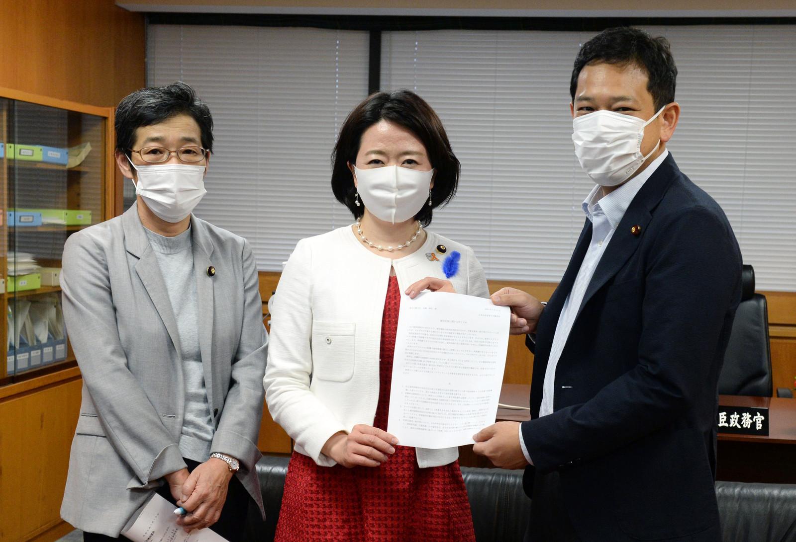 自見大臣政務官(中央)に申し入れ書を手渡す倉林(左)、宮本の各氏
