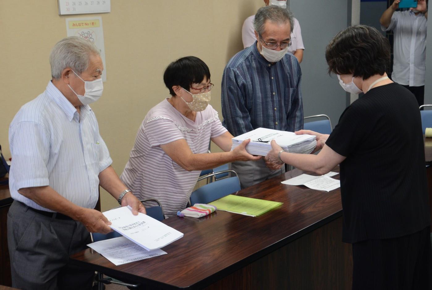 新宿区健康部長(右)に署名を提出する人たち
