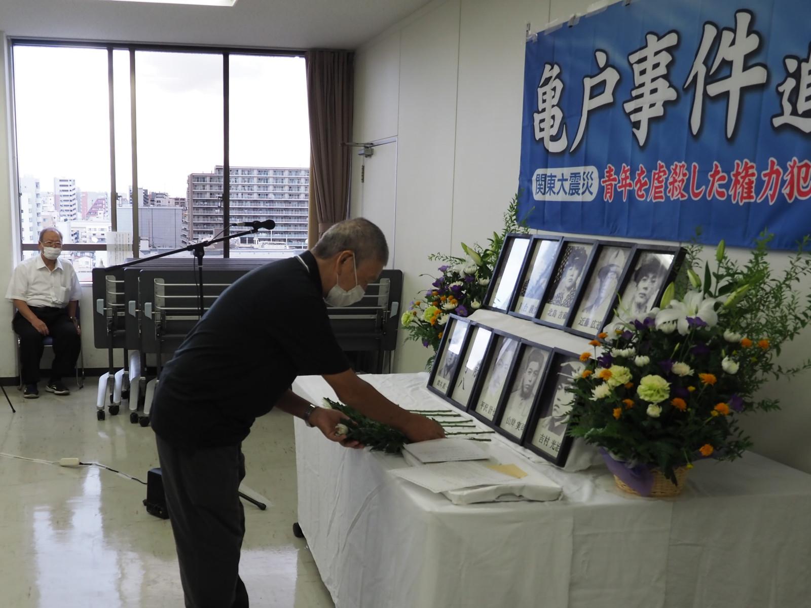 虐殺された若者たちの遺影などの前に献花する参列者