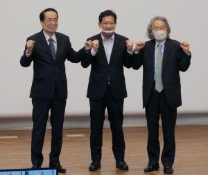 参加者の声援にグータッチで応える(左から)菅、宮本、広渡の各氏
